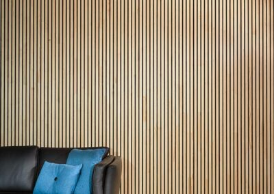Wooden covering for ceiling and wall in a living room with a sofa (NORTO Bech)