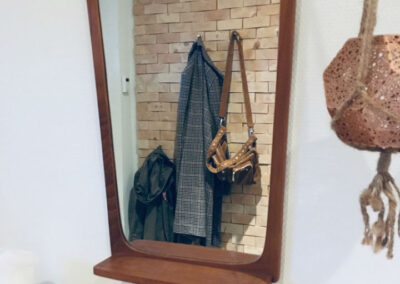Hallway with jacket and a bag placed on a wall decoration. Mirror and a shelve