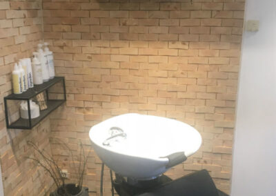 Untreated wall decoration in a corner in a hair dressing salon. Black shelves mounted on the wall and a chair in the front