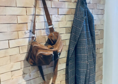 Wall decoration of solid pine wood in a hallway. Hocks on the wall and a jacket and a bag.