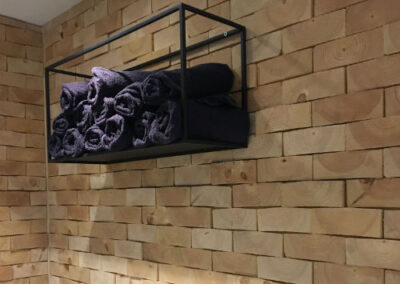 Wooden wall covering of solid pine wood blocks. Shelve mounted on the wall