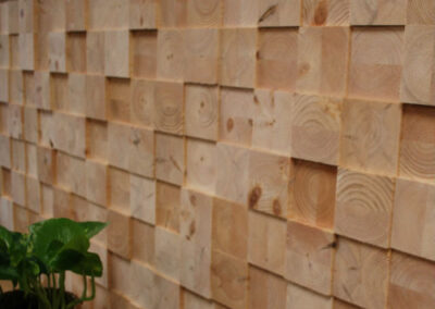 Wooden wall decoration of face blocks. Bench with a plant