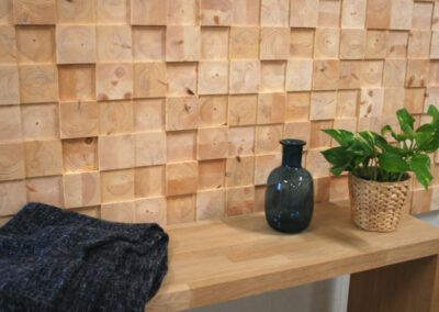 Wooden wall covering of face blocks. Bench with a blanket, vase and flower