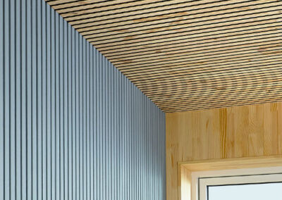 Wooden raw and painted coverings on ceiling and walls in a room with a window