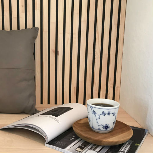 Wooden wall covering of black painted slats. Pillow, magazine and a cup of coffee placed in a bench