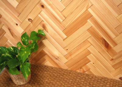 Wooden wall decoration mounted in a herringbone pattern. A flower is placed on a mat.