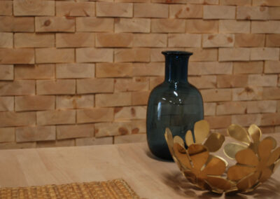 Wooden wall decoration of raw face blocks. A vase and a bowl standing on a table of wood