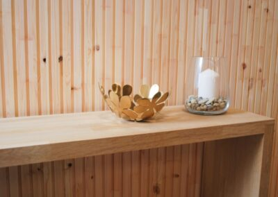 Untreated wooden wall covering of slats and a bench of wood
