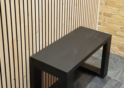 Wooden wall covering of slats with black painted grooves and a black bench